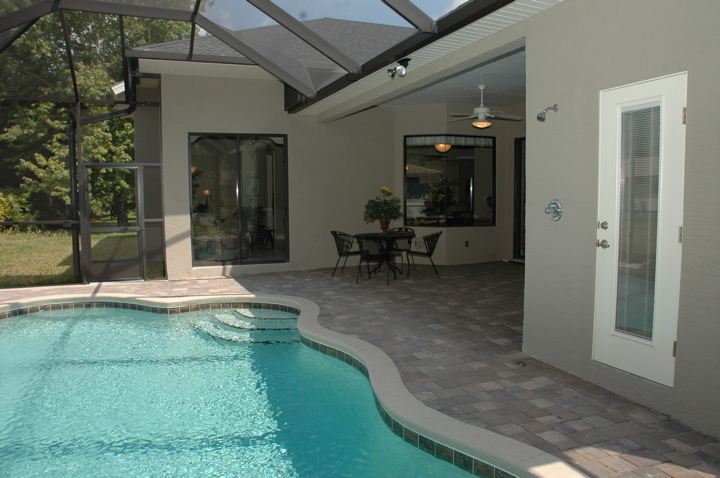 Lanai with table and chairs next to sparkling pool
