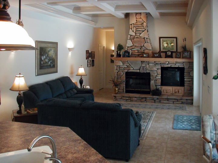 Living room with ceiling details and stone fireplace