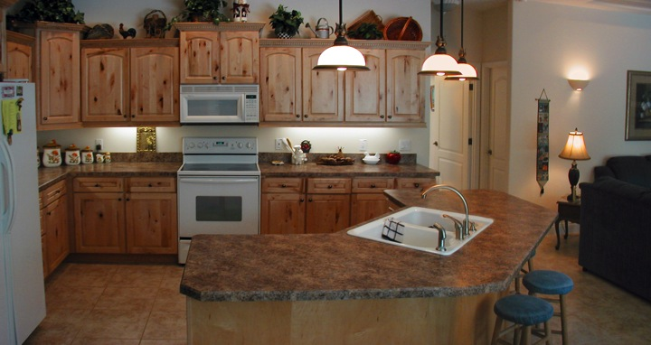 Rustic wood cabinets in an open kitchen with kitchen island