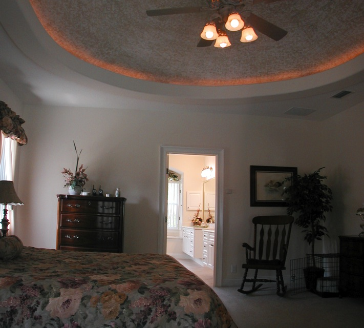 Master bedroom with inset lighting on ceiling and door to master bathroom
