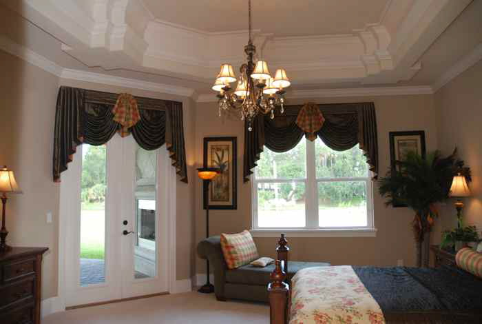 Master bedroom of a custom built home with custom chandelier
