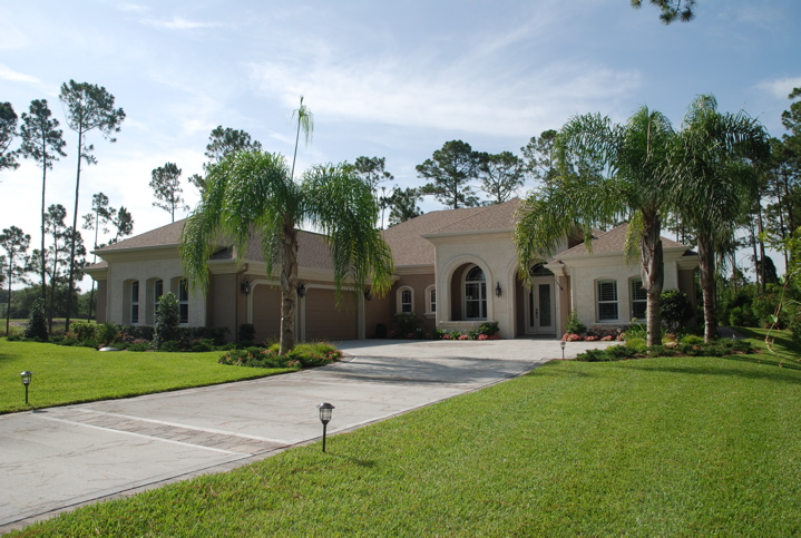 Model home with three car garage and lush green grass