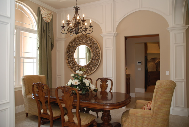 Dining table with large decorative circular mirror hanging on the wall.