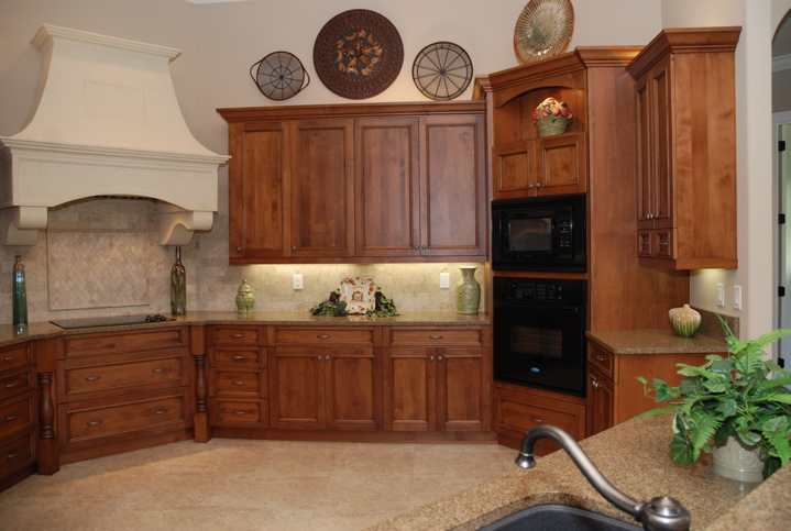 Medium colored wood cabinets in kitchen with white stove hood