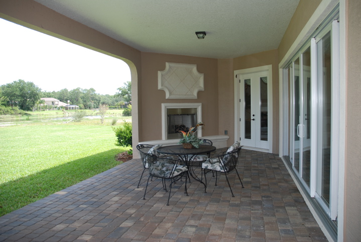 Outdoor lanai with dining furniture and fireplace