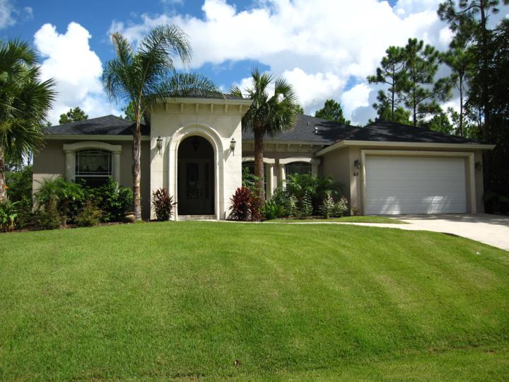 Perfectly manicured lawn of home with tall arch entryway