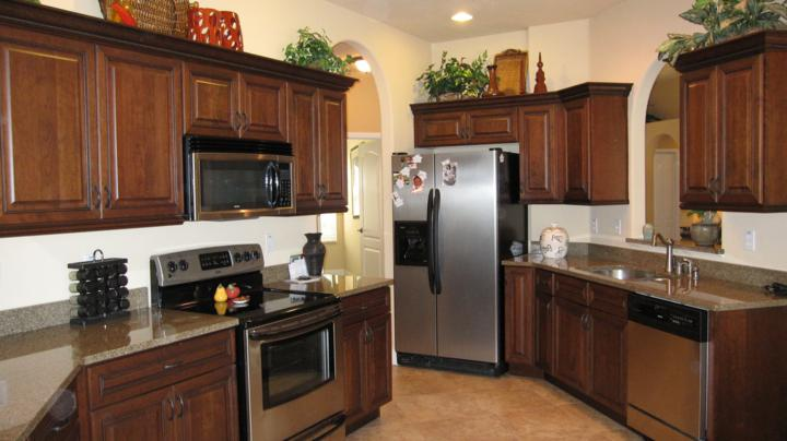 Large custom kitchen with dark wood custom cabinets and stainless steel appliances