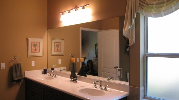 Double vanity sink in master bathroom with track lighting above mirror
