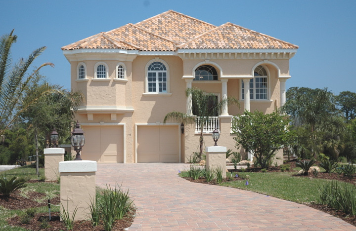 Custom home with arch windows and matching clay roof shingles