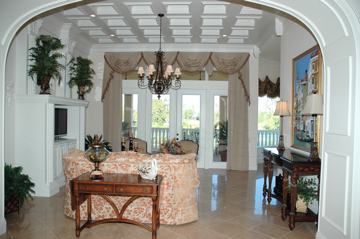 Custom ceiling details in living room with french doors leading to deck