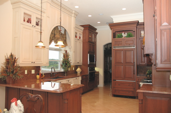 Brown cabinets in a custom kitchen with marble countertops