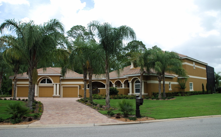 Brown three car garage home with white trim and palm trees in yard