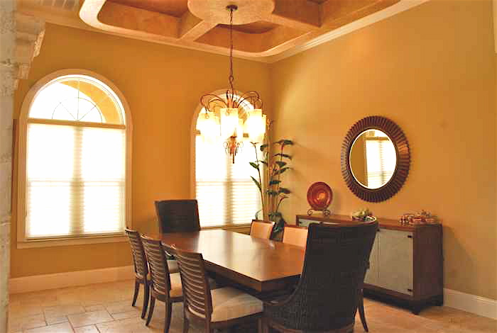 Tan dining area with chandelier hanging above dining table