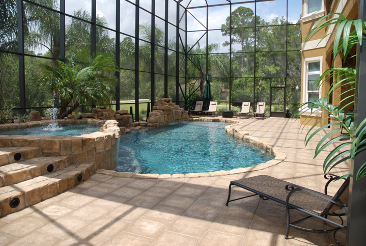 In ground pool with stone details enclosed in a glass lanai