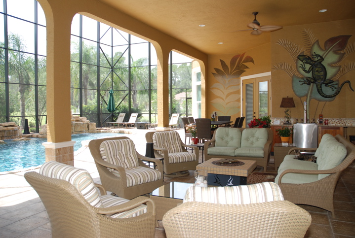 Wicker outdoor living furniture inside a glass lanai