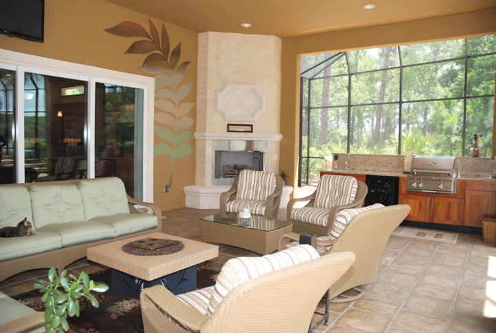Outdoor kitchen and wicker furniture with fireplace in the background