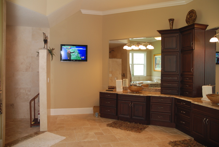 Master bathroom with ample storage in deep brown cabinets