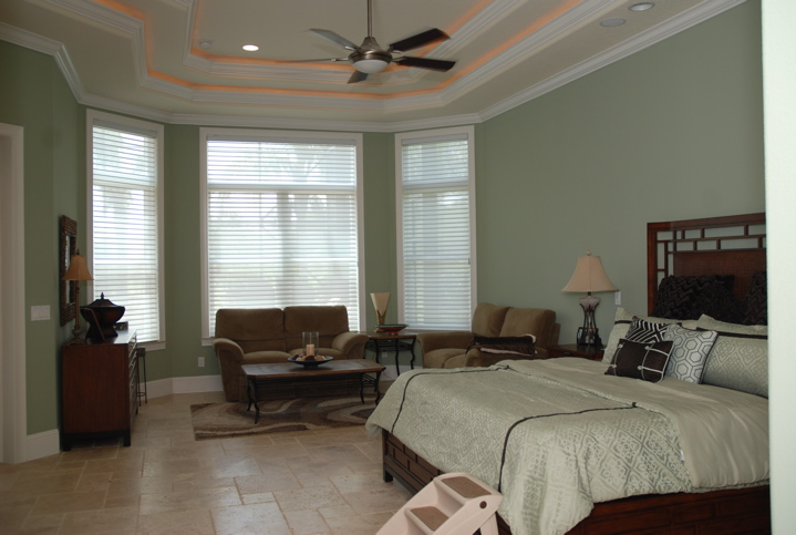 Spacious master bedroom with white trim and light green walls