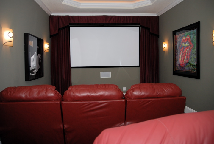 Home theater with white projection screen and leather chairs