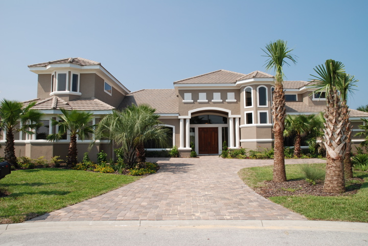 Tannish grey home with white trim details and custom drive way