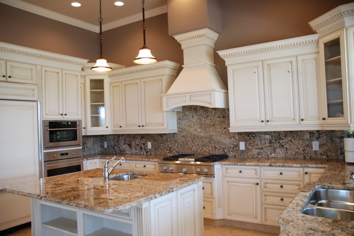 Dark brown wall with white kitchen cabinets and white hood