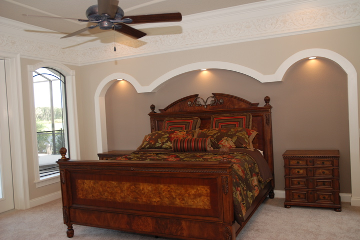 Master bedroom with decorative wall cut out and recessed lighting