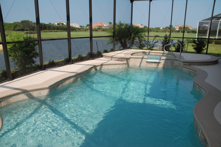 In ground pool inside a covered lanai overlooking a body of water