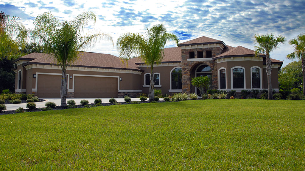 Front of home with green grass and blue sky with clouds