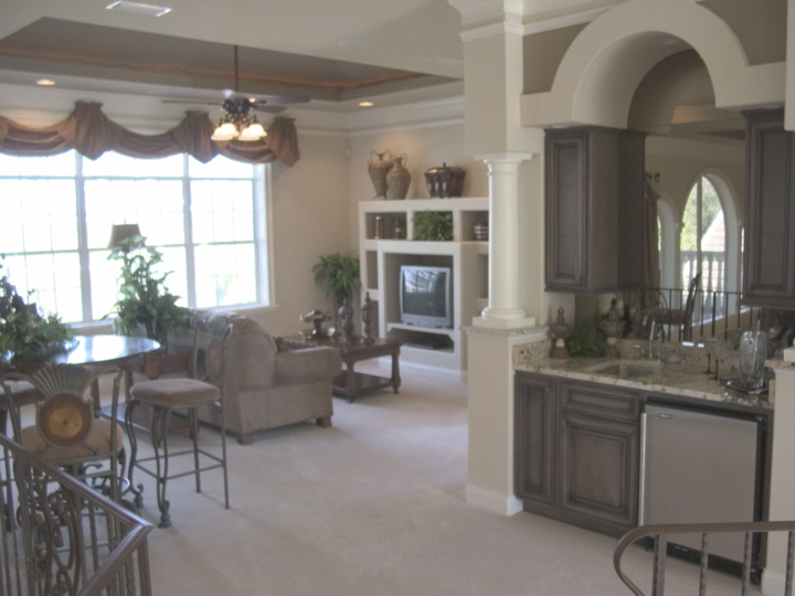 Open floor plan with bar area, dining area and living area