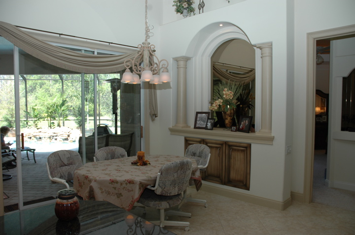 Dining area with large sliding glass doors leading to the lanai with in ground pool