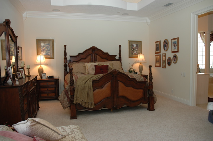Master bedroom featuring a grand four poster bed and white crown molding