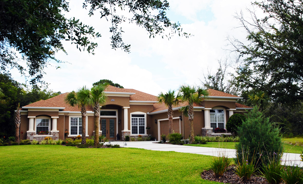 Brown home with white trim and lush green grass in the lawn
