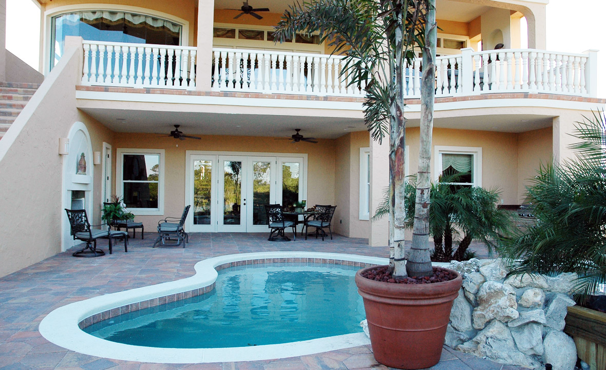 Outdoor in ground pool surrounded by custom stone work tile
