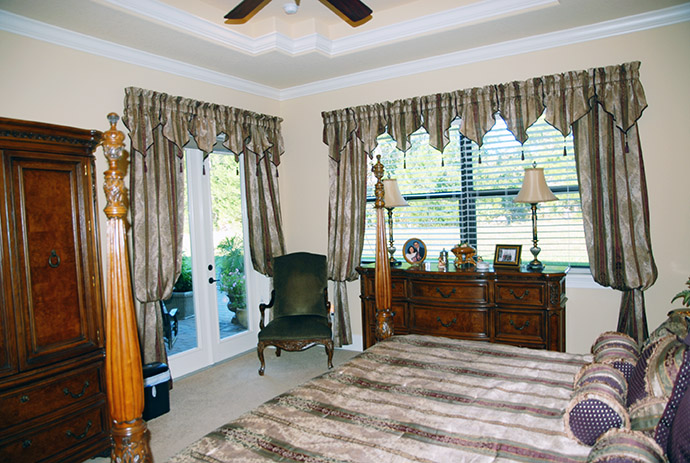 Master bedroom with striped drapes framing the windows and french doors