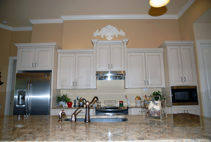 White kitchen cabinets featuring silver appliances and marble counter tops