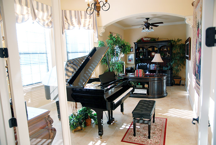 Grand piano bathed in natural light in front of large windows