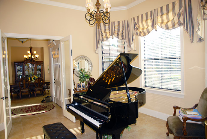 Grand piano in front of interior french doors