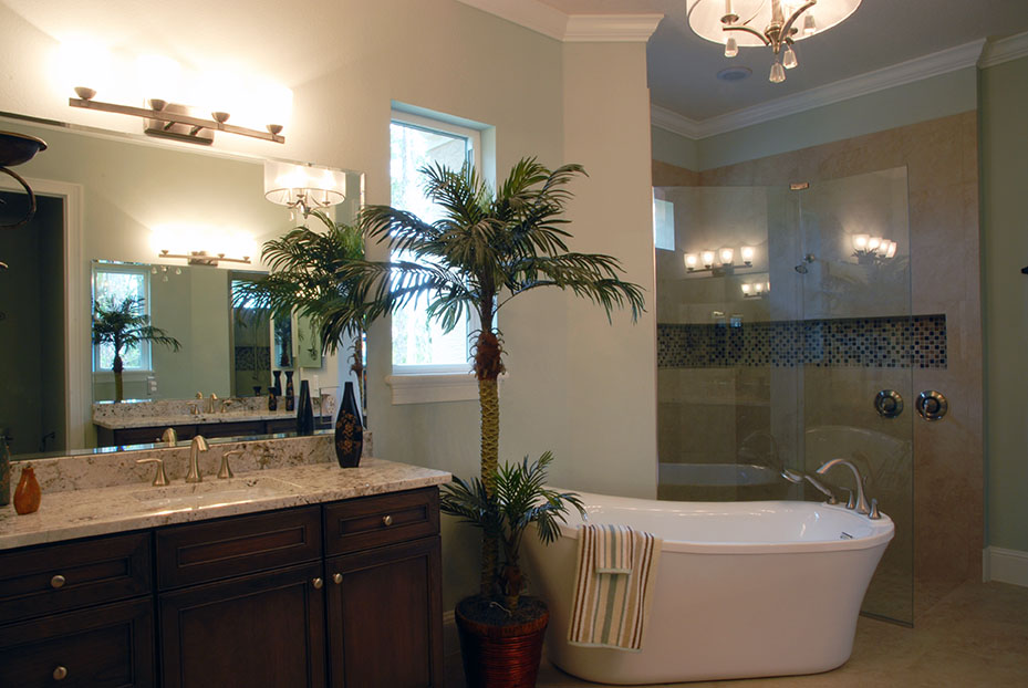 Mini palm tree in master bathroom next to large soaking tub