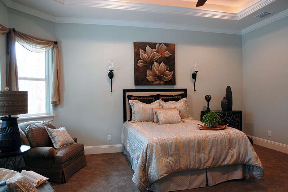 Large light blue bedroom with crown molding and ceiling details