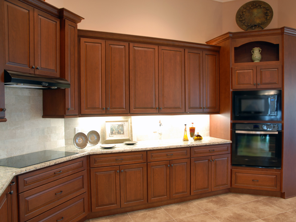 Wood cabinets in kitchen with flat top stove, microwave and oven