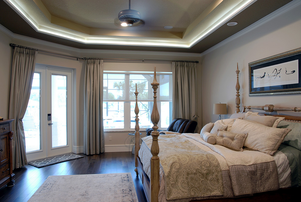 Master bedroom with four poster king size bed and french doors leading to the lanai