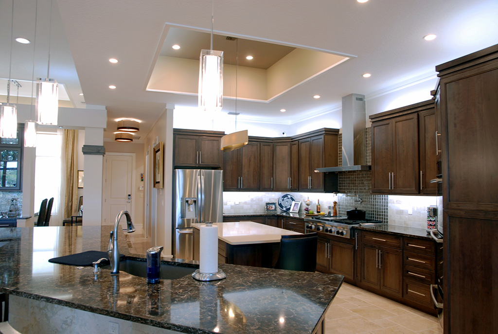Dark custom cabinets in kitchen with bar shaped pulls and marble counter tops