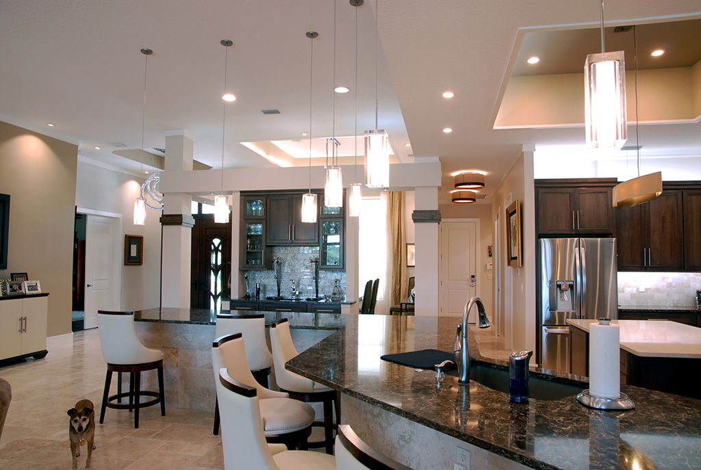 Large kitchen area with dark marble counter tops and rectangular drop pendant lighting
