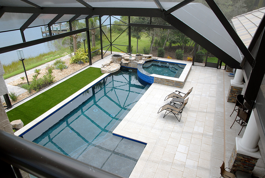 Glassed in lanai with in ground pool and hot tub