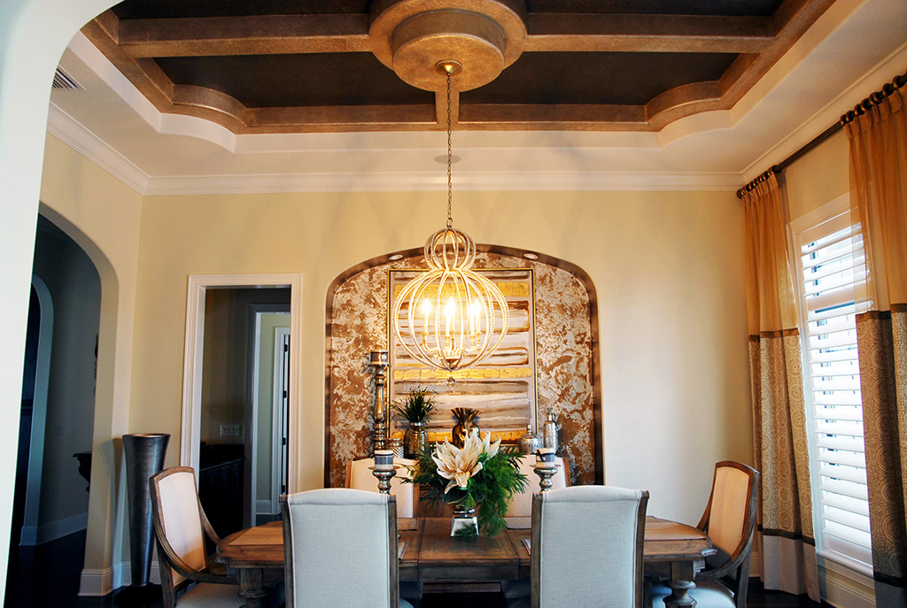 Formal dining area with elegant chandelier hanging from a ceiling with details