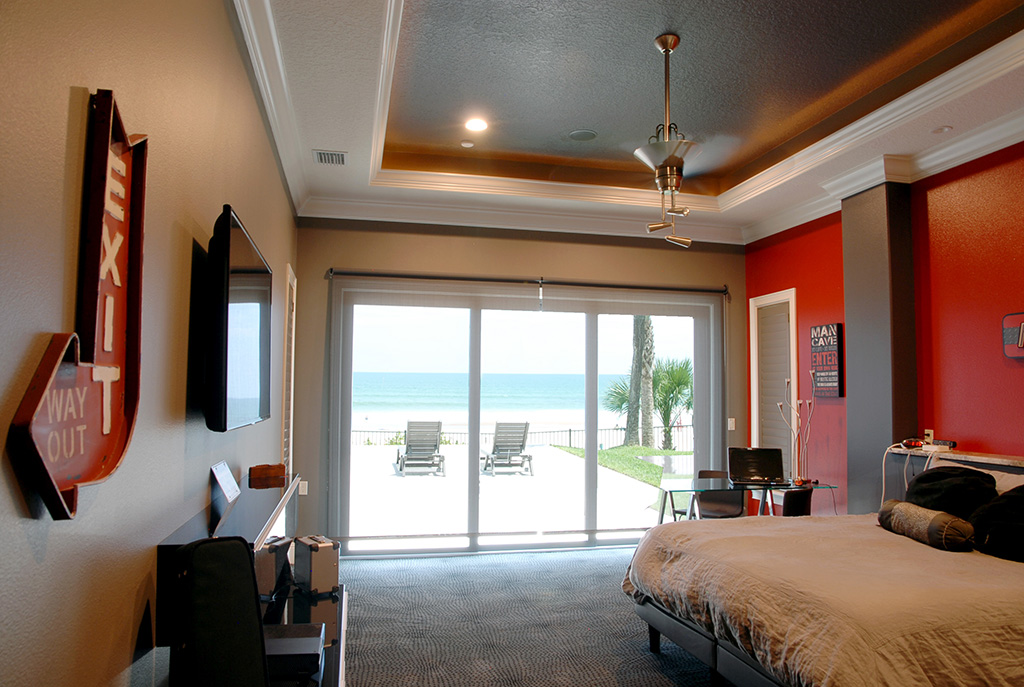 Bedroom with sliding glass doors leading out door to the beach