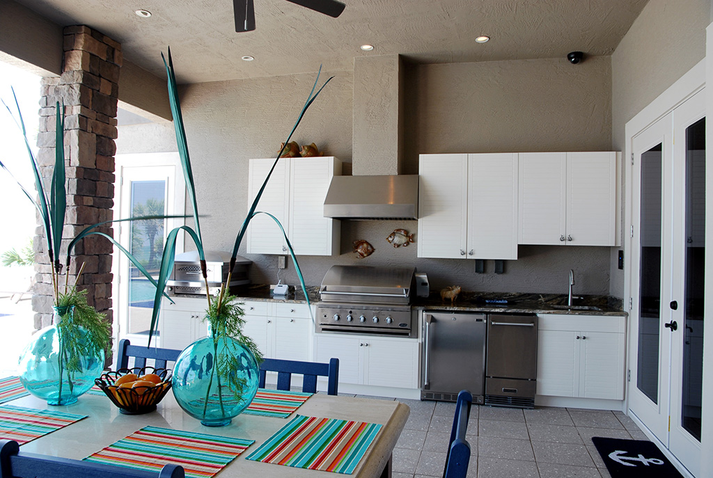 Outdoor kitchen with stainless steel appliances and white cabinets