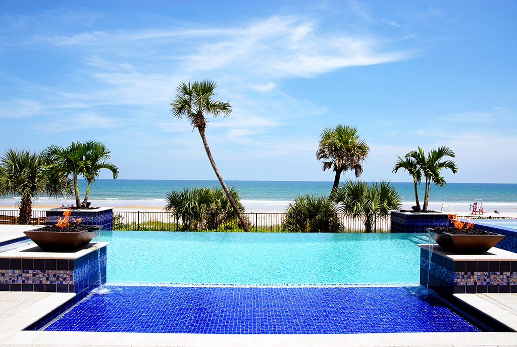 Outdoor pool overlooking the ocean and palm trees