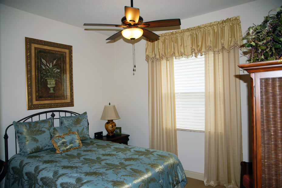 Bed with blue and gold linens and gold curtain