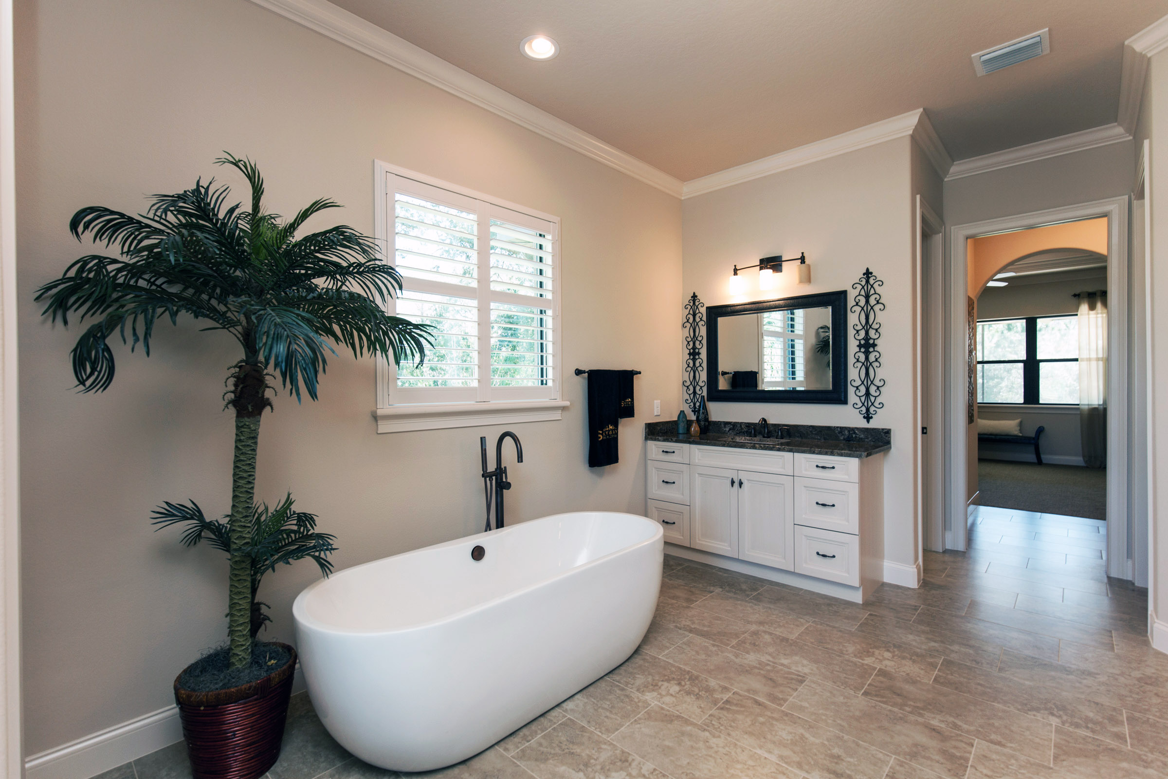 Large bathtub and with potted tree and single vanity sink.